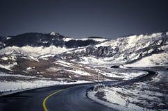 Camino con las curvas en una montaña con nieve imagenes de archivo