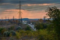 Camino con los pilones de alto voltaje del poder Fotos de archivo