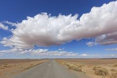 Camino con paisaje del desierto y el cielo azul nublado. Imagen de archivo