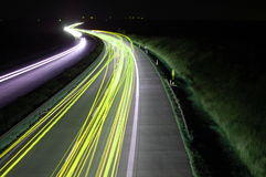 Camino con tráfico de coche en la noche con las luces borrosas Fotos de archivo libres de regalías