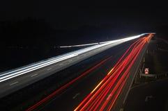 Camino con tráfico de coche en la noche con las luces borrosas foto de archivo libre de regalías
