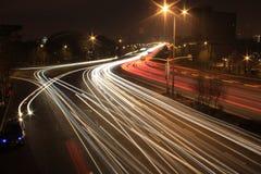 Camino con tráfico de coche en la noche con las luces borrosas Imagenes de archivo