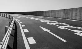 Camino concreto con símbolo de la flecha en la montaña en s blanco y negro foto de archivo