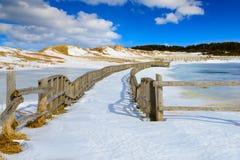 Camino congelado marcado por la cerca de madera Fotos de archivo libres de regalías