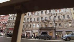 Camino congestionado con los coches todav?a que se colocan al lado de la calle con las fachadas de los edificios metrajes