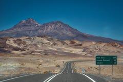 Camino cubierto de alquitrán con el poste indicador y las montañas rugosas imagenes de archivo