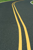 Camino Curvy con la línea amarilla doble Imagen de archivo libre de regalías