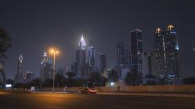 Camino de Dubai con tráfico de coche en el fondo del centro de ciudad en la noche almacen de metraje de vídeo