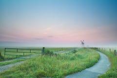 Camino de la bicicleta al molino de viento en niebla de la salida del sol Imagen de archivo libre de regalías