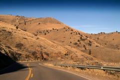 Camino de la carretera con las colinas Foto de archivo libre de regalías