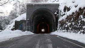 Camino de la montaña con el túnel de piedra antiguo en el invierno escénico