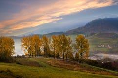 Camino de la montaña con los árboles a lo largo de una trayectoria con un pueblo de montaña Fotos de archivo libres de regalías