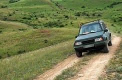 Camino de la montaña de la travesía del coche de SUV del tracción cuatro ruedas Fotos de archivo