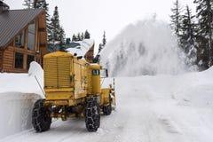 Camino de la montaña del claro de la máquina de la retirada de la nieve por las cabinas Imagen de archivo