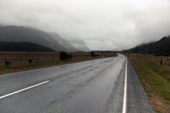 Camino de la montaña del país en lluvia y nubes Fotografía de archivo libre de regalías