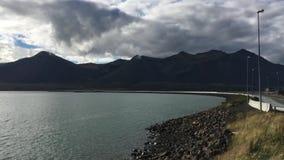 Camino de la montaña de Islandia cerca del lago con los coches almacen de metraje de vídeo