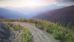 Camino de la montaña de la puesta del sol del viajero del hombre que camina almacen de video