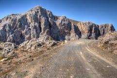 Camino de la montaña que pasa los acantilados rocosos rugosos Imágenes de archivo libres de regalías
