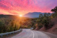 Camino de la montaña que pasa a través del bosque con el cielo colorido dramático y las nubes rojas en la puesta del sol colorida Foto de archivo libre de regalías