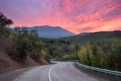 Camino de la montaña a través del bosque en la puesta del sol colorida Fotografía de archivo libre de regalías