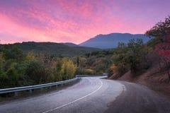 Camino de la montaña a través del bosque en la puesta del sol colorida Foto de archivo libre de regalías