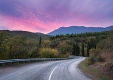 Camino de la montaña a través del bosque en la puesta del sol colorida Viaje detrás Imágenes de archivo libres de regalías