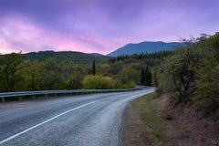 Camino de la montaña a través del bosque en la puesta del sol colorida Viaje detrás Fotografía de archivo libre de regalías