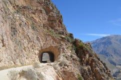 Camino de la montaña a través del túnel Carretera en un área montañosa cerca de las cuestas rocosas de la piedra fotografía de archivo libre de regalías