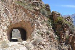 Camino de la montaña a través del túnel Carretera en un área montañosa cerca de las cuestas rocosas de la piedra imagen de archivo