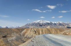 Camino de la mucha altitud con el fondo capsulado nieve de la montaña Foto de archivo