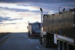 Camino de la tarde cuesta arriba con del convoy los camiones semi con los remolques a granel fotografía de archivo libre de regalías