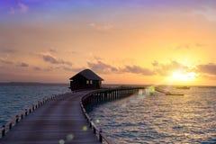 Camino de madera de la isla a una choza sobre el agua en una puesta del sol maldives imagen de archivo