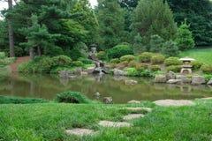 Camino de piedra que lleva abajo a la vista de Koi Pond y de la piedra Imagen de archivo libre de regalías