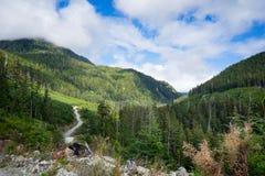 Camino de saca de enrrollamiento aunque un valle montañoso imagen de archivo libre de regalías