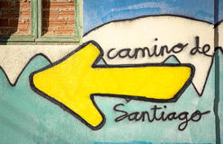 Camino de Santiago words and a yellow arrow painted on a wall on the way of Santiago. The Camino de Santiago words and a yellow arrow painted on a wall on the Royalty Free Stock Image