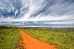 Camino de tierra anaranjado rural con el cielo azul y el horizonte lejano imagen de archivo