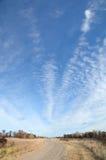 Camino de tierra con las nubes de Altocumulus Foto de archivo