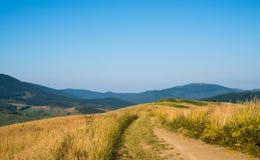 Camino de tierra contra el paisaje en el Moun cárpato ucraniano imagen de archivo libre de regalías