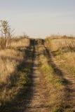 Camino de tierra del país que pasa la colina foto de archivo