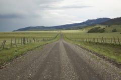 Camino de tierra en el valle centenario, Montana con la tormenta entrante, los campos verdes y las montañas Foto de archivo