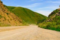 Camino de tierra entre las colinas escarpadas imágenes de archivo libres de regalías