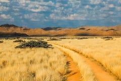 Camino de tierra entre las nubes, las montañas y el desierto en la puesta del sol Imagenes de archivo