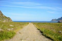 Camino de tierra largo abajo al océano azul Fotos de archivo