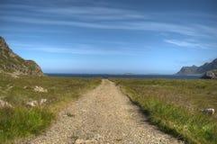 Camino de tierra largo abajo al océano azul Imagen de archivo