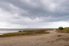 Camino de tierra a lo largo del coste del mar, nube de tormenta Foto de archivo libre de regalías