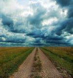Camino de tierra a través de la pradera en tormenta Foto de archivo libre de regalías