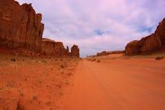 Camino de tierra a través del valle del monumento, Utah, los E.E.U.U. Imagen de archivo libre de regalías