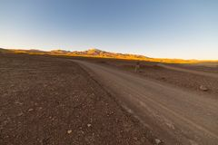Camino de tierra vacío en cordillera estéril de la mucha altitud en las montañas de los Andes en la manera a la sal famosa de Uyu Foto de archivo libre de regalías
