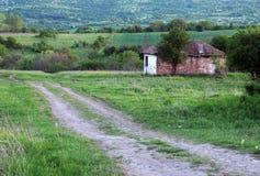 Camino de tierra y casa abandonada Imagen de archivo libre de regalías