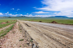 Camino de tierra y cielo azul, estepa mongol Foto de archivo